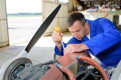 Mekaniker som arbetar p? flygplan fotografering för bildbyråer