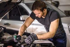 Mekaniker som arbetar under bilhuven i reparationsgarage arkivfoto