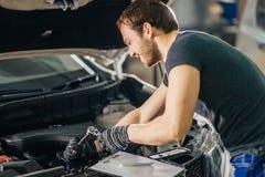 Mekaniker som arbetar under bilhuven i reparationsgarage royaltyfri fotografi