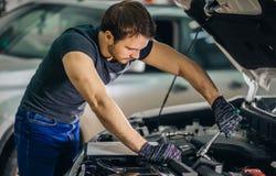 Mekaniker som arbetar under bilhuven i reparationsgarage arkivbild