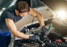 Mekaniker som arbetar under bilhuven i reparationsgarage royaltyfria bilder