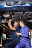 Mekaniker som arbetar under lyftbilen arkivbild