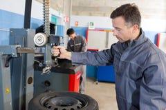 Mekaniker som balanserar hjulet med maskinen på garaget arkivbild