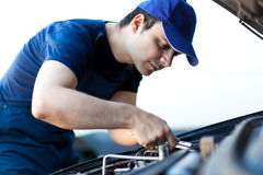 Mekaniker som fixar en bilmotor arkivbild