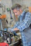 Mekaniker som fixar en chainsaw arkivfoto