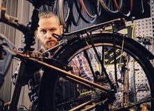 Mekaniker som gör handboken för service för cykelhjul i ett seminarium arkivbilder