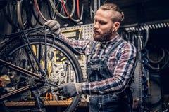 Mekaniker som gör handboken för service för cykelhjul i ett seminarium fotografering för bildbyråer
