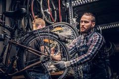 Mekaniker som gör handboken för service för cykelhjul i ett seminarium royaltyfria bilder