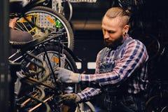 Mekaniker som gör handboken för service för cykelhjul i ett seminarium royaltyfria foton