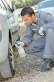 Mekaniker som gör ren ett däck arkivfoton