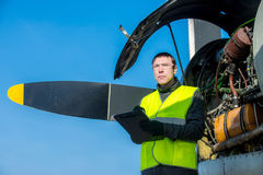 Mekaniker som kontrollerar airplane& x27; s-motor royaltyfri foto
