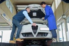 Mekaniker som kontrollerar bilmotorn royaltyfri foto