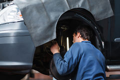 Mekaniker som kontrollerar bilupphängningsystemet royaltyfri foto