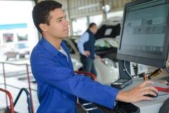 Mekaniker som kontrollerar den moderna elektroniska diagnostiska tabellen arkivfoton
