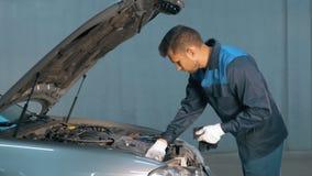 Mekaniker som kontrollerar den olje- nivån i ett bilseminarium Man i lastbilservicemotor royaltyfri bild