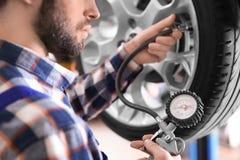 Mekaniker som kontrollerar gummihjultryck i tjänste- mitt royaltyfri fotografi