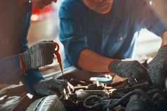Mekaniker som kontrollerar motorn royaltyfri foto