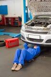Mekaniker som ligger och ser under bilen Royaltyfri Foto