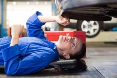Mekaniker som ligger och ser under bilen royaltyfri fotografi