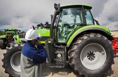 Mekaniker som pekar på den stora traktoren royaltyfri fotografi