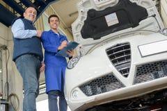 Mekaniker som poserar bredvid den vita bilen royaltyfria bilder