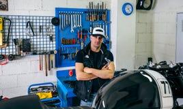 Mekaniker som poserar med en motorcykel royaltyfri fotografi