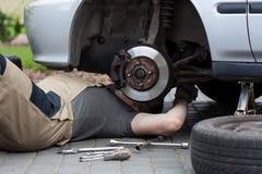 Mekaniker som reparerar bilhjulet arkivbild