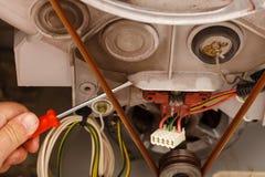 Mekaniker som reparerar tvagningmaskinen arkivbild