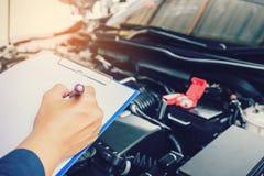 mekaniker som rymmer en skrivplatta av tjänste- beställning som arbetar i garage arkivfoton