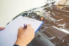 mekaniker som rymmer en skrivplatta av tjänste- beställning som arbetar i garage royaltyfri fotografi