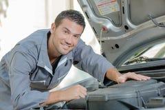 Mekaniker som stås av bilen arkivbild