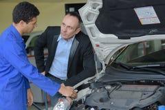 Mekaniker som talar till klienten i garage fotografering för bildbyråer