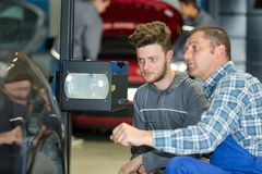 Mekaniker som testar billjus i garage royaltyfria bilder