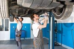 Mekaniker som tillsammans arbetar, teamworkreparationsbil arkivbilder