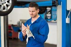 Mekaniker som torkar händer med trasan arkivfoto
