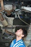 Mekaniker som undersöker avgasröret av en bil arkivbild