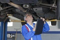 Mekaniker som undersöker mycket noggrant bilen och ner skriver något på skrivplattan arkivfoto