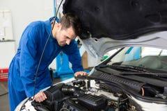 Mekaniker som undersöker under huven av bilen arkivbilder