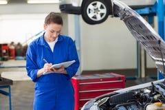 Mekaniker som undersöker under huven av bilen royaltyfri bild