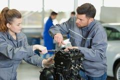 Mekaniker som vägleder lärlingen som arbetar på motorn fotografering för bildbyråer