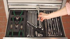 Mekaniker som väljer det nödvändiga hjälpmedlet för att arbeta i service för automatisk reparation lager videofilmer