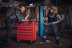 Mekaniker två har gyckel, medan reparera en bil i ett garage Fotografering för Bildbyråer