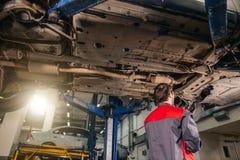 Mekaniker under bilen i examing gummihjul för garage och tekniskt villkor arkivbild