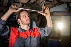 Mekaniker under bilen i examing gummihjul för garage och tekniskt villkor fotografering för bildbyråer