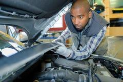 Mekaniker under bilhättan royaltyfri bild