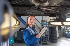Mekaniker under en bil under en periodisk undersökning fotografering för bildbyråer
