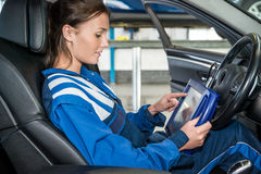 Mekaniker Using Digital Tablet i bil på garaget arkivbild