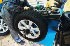 Mekanikerarbetaren gör datoren raden att rulla att balansera på det speciala utrustningmaskinhjälpmedlet i reparationsservice Royaltyfri Fotografi