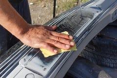 Mekanikerarbetarrepairman som sandpapprar den polerande bilstötdämparen och förbereder stötdämparen för att måla under reparation Royaltyfria Bilder
