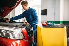 Mekanikerkontroller luftar det betingande systemet i bil arkivfoton